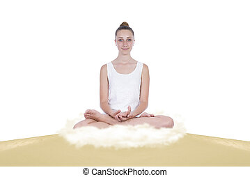 Girl in yoga lotus position on a sand dune, below her an...