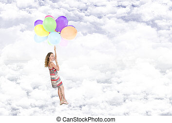 Girl hanging on balloons flying in the clouds