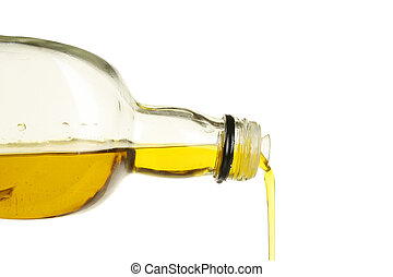 Olive oil pouring from a glass bottle against white