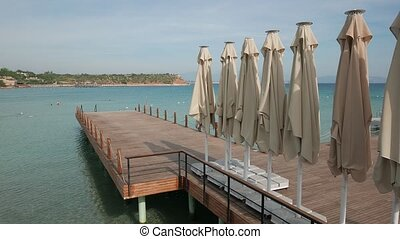Wooden bathing pier with line of umbrellas ready for...