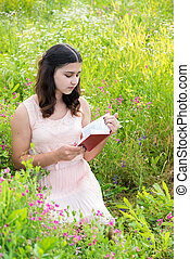 dark-haired girl reading a book on nature - dark-haired girl...
