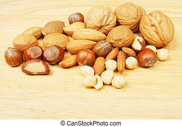 Whole and shelled nuts on a wooden board