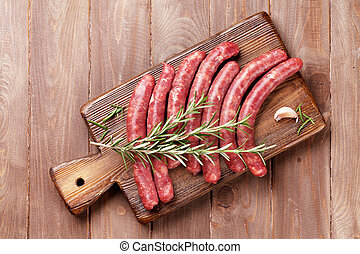 Raw sausages and ingredients for cooking. Top view on wooden...