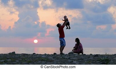 Schislivaya family: father, mother, baby son on the rocky sea beach during sunset. Parents play and kiss baby in the rays of the red sun and blue sky