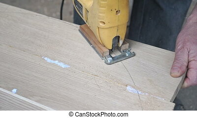 Carpenter is cutting a board with fretsaw - Carpenter is...