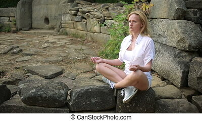 woman sitting and meditating on stone dolmen - Traveler...
