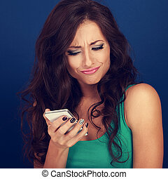 Cranky surprisung grimacing young woman reading sms on...