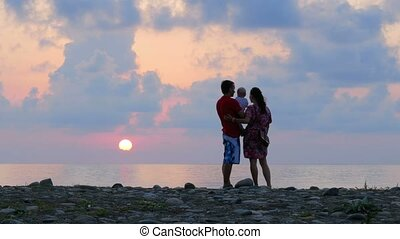 Schislivaya family: father, mother, baby son on the rocky sea beach during sunset.
