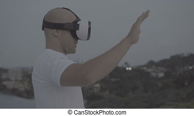 Man uses a virtual reality glasses on the roof - Man having...