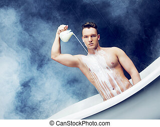 man taking a bath - attractive young man taking a bath with...
