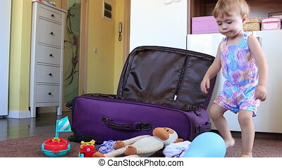 small child puts clothes and toys in the suitcase