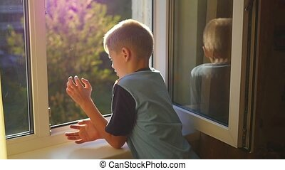 the child looks at the open window - the beautiful child...