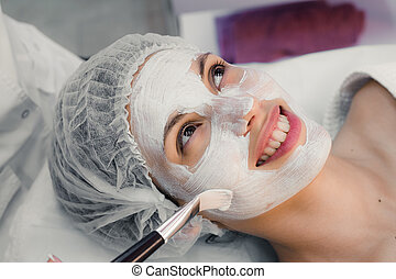 Young woman at spa procedures applying mask