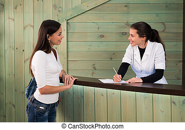 Profile view of a cute brunette welcomes customer register...