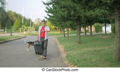 Young man tourist is with a large suitcase on wheels around the city park.