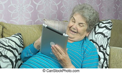 Woman looks at pictures using a digital tablet - Elderly...