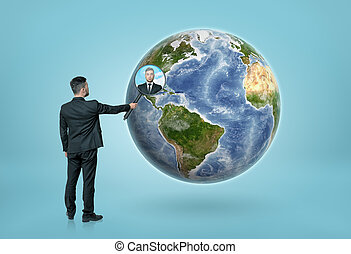 Businessman looking through magnifying glass on Earth - Back...
