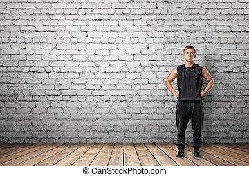 Front view of muscled young man standing with his hands on...