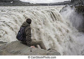Young man on the edge contemplating Detifoss waterfall in Iceland.