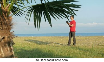 The man on the rocky beach. Palm tree in the foreground. The man is looking at the tablet right road.