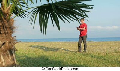 The man on the rocky beach. Palm tree in the foreground. The...