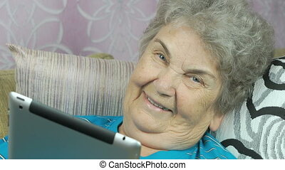 Old woman holds a tablet computer indoors - Old woman lying...