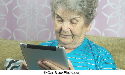 Senior Woman Uses Computer Tablet At Home
