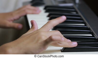 the hand on piano key in close-up shot child learning to...