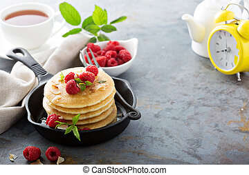 Stack of fluffy buttermilk pancakes with fresh raspberry