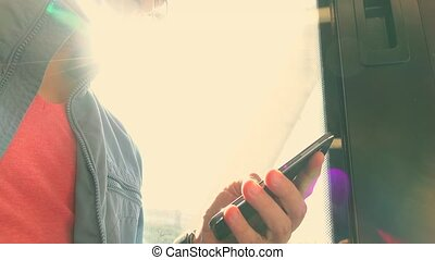 Man using his smartphone in the train. Tapping on device...