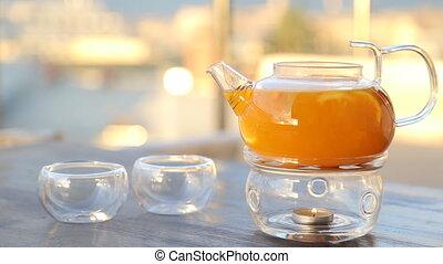 kettle with sea-buckthorn tea on the table.