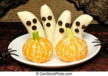 Healthy Halloween treats, banana ghosts and orange pumpkins,...