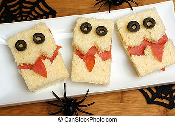 Fun Halloween monster sandwiches on a plate with wood...