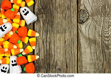 Halloween candy side border against a rustic wood background
