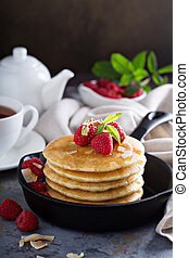 Stack of fluffy buttermilk pancakes with fresh raspberry in...