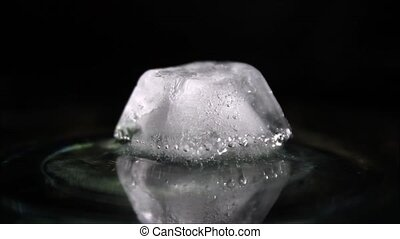 Melting ice cube with air bubbles inside