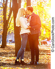 Young couple hugging and flirting in park. - Young couple...