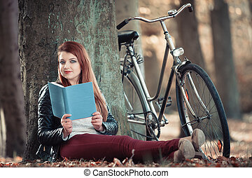 Woman reading book under tree, outdoors activity and relax...