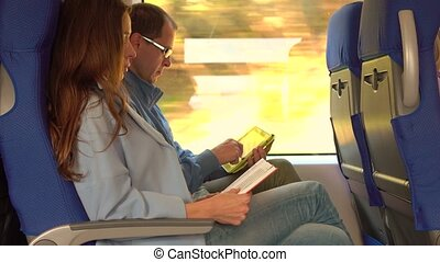 Couple travelling by train. Girl reading a book and man using his tablet computer.