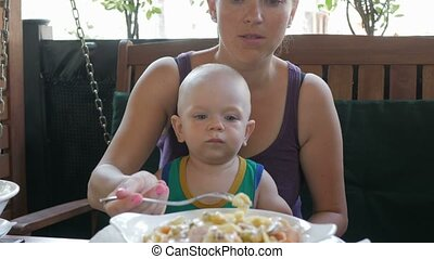 Young mother is feeding the baby on her lap pasta in Italy....