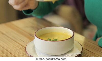 Attractive woman eating tasty soup in cafe.
