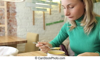 Happy, beautiful woman eating tasty soup in cafe in the...