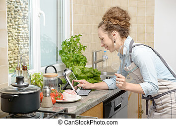 smiling young woman using a tablet for cooking