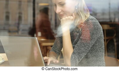 Businesswoman working on laptop and drinking coffee in cafe