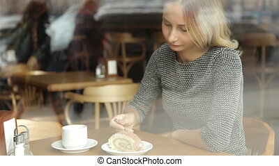Woman eating delicious cake and drink coffee in cafe.