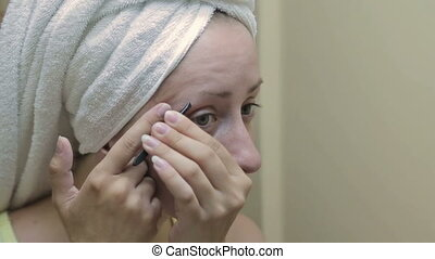 Beautiful woman plucking her eyebrows in front of mirror -...