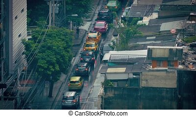 Cars Passing Slums On Rainy Day - High angle view of traffic...