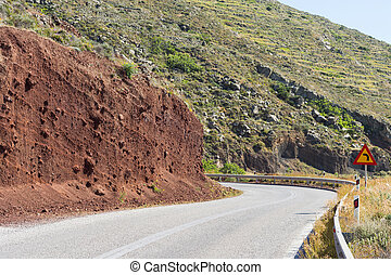 Turn left warning sign on a curve empty road Brown cliff on...