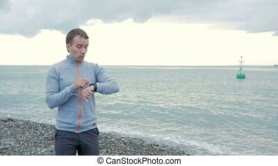 A man walks along the beach and check the messages on the...