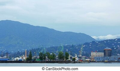 Port is near the sea and the mountains, which is waiting for a ship. Clouds spread over the mountains